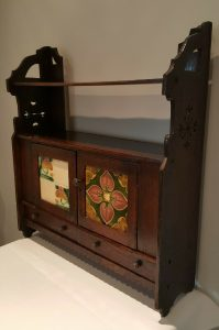 Arts & Crafts hanging oak wall cupboard with tiled doors, drawers and shelves