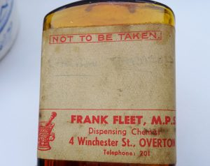Antique amber Not To Be Taken poison bottle, old label Carbon Tetrachloride, Frank Fleet MPS, Dispensing Chemist, 4 Winchester St, Overton