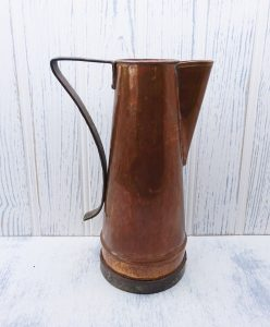 Arts & Crafts copper pitcher with iron handle and base rim, hammered copper in bark pattern.