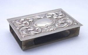 Antique silver metal matchbox holder featuring a Baroque acanthus leaf design with blank cartouche
