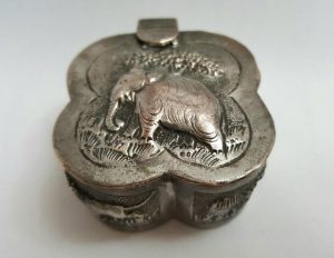 Indian silver plated box, a lidded quatrefoil shaped box/pot with repousse decoration, a trinket pot with lions, tiger, deer and elephant