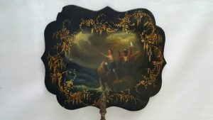 Regency circa 1820 lady's hand-held face fire screen depicting Crusoe and Friday hailing a distant ship in rough sea