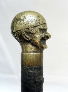 Antique brass topped leather bound stick / cane featuring a quirky and happy looking fellow wearing a cap at a jaunty angle