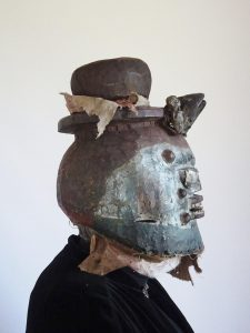 Vintage African helmet mask, a 'Witch Doctor' carved hollowed scary wooden mask with cloven hooves and figures attached - aspects of voodoo