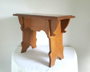 an Elizabethan style solid oak trestle type stool in the 20th Century Arts & Crafts revival manner,