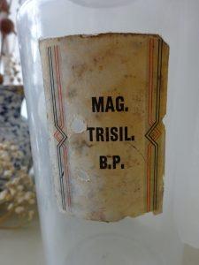 Vintage clear hand blown pharmacy bottle with glass stopper, original label for Mag. Trisil. BP chemist bottle, pontil scar on base