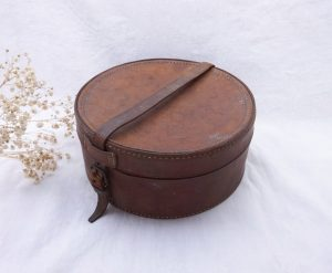 Antique leather collar box, round tan leather storage or craft box with strap closure, old Edwardian or early 20th Century box for collars